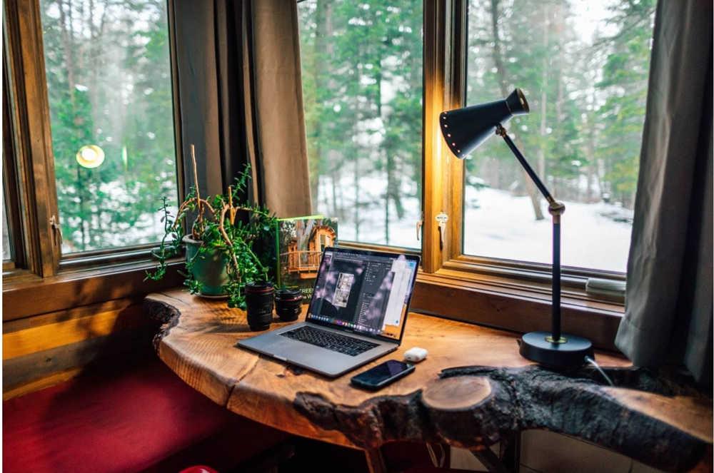 A home office live edge desktop in a corner window